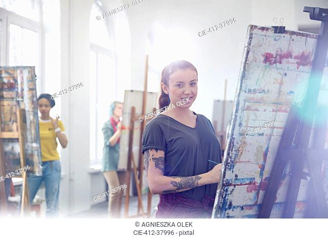 Portrait smiling female painter with tattoos painting in art class studio