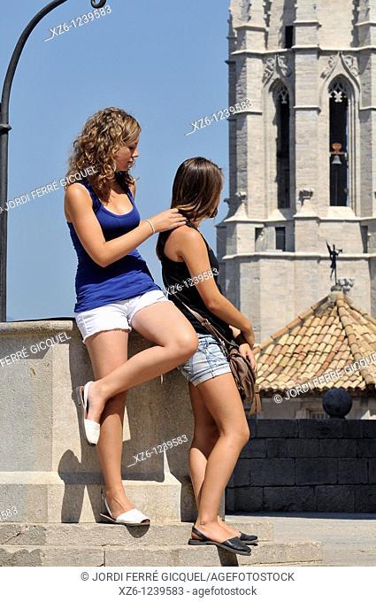 Two girls posing front Sant Feliu Church, Girona, Catalonia, Spain, Europe