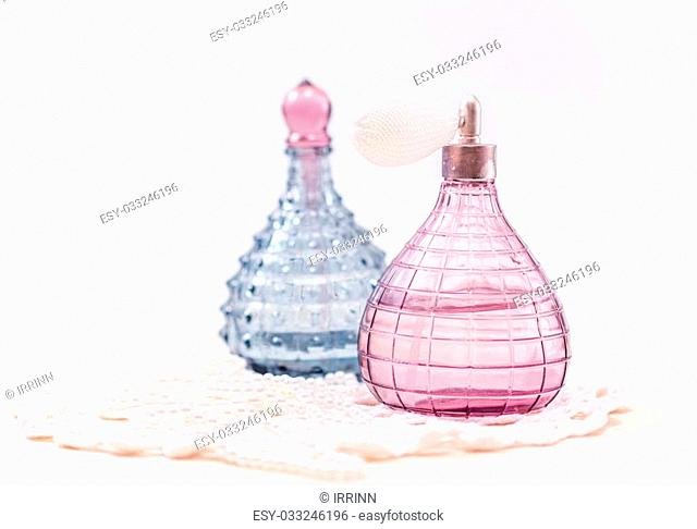 Two glass bottles of female perfume on a white background. Pink toning