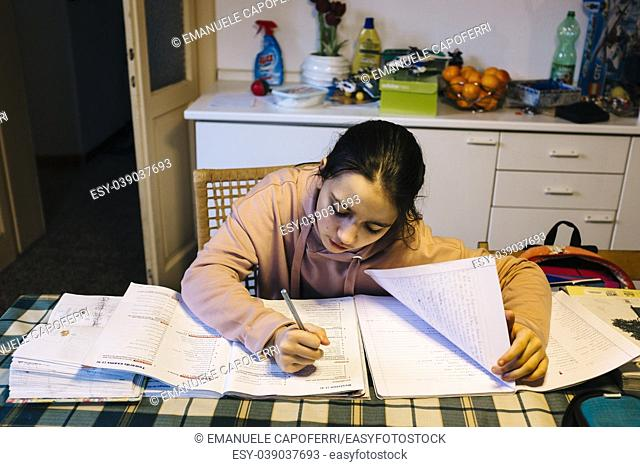 teenager performs school homework in the home kitchen on the table