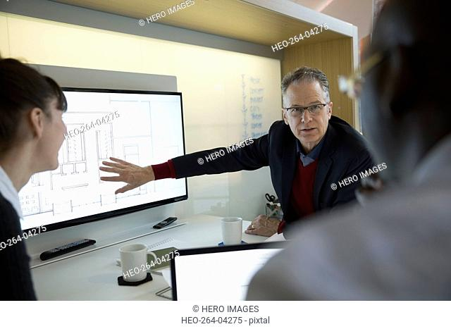 Architect discussing digital blueprint on monitor in meeting