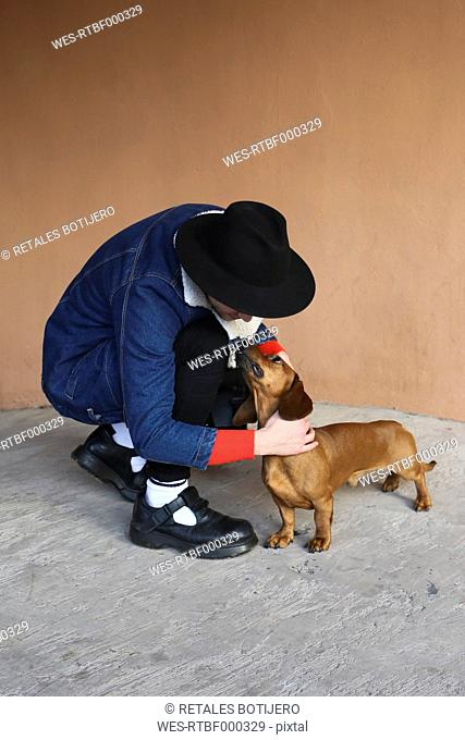 Young man petting his dachshund outdoors