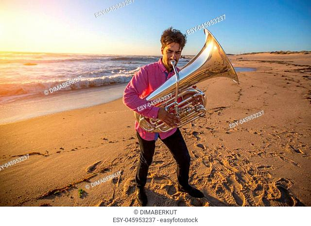 Young musician play the trumpet on rocky sea coast during surf. Tuba instrument