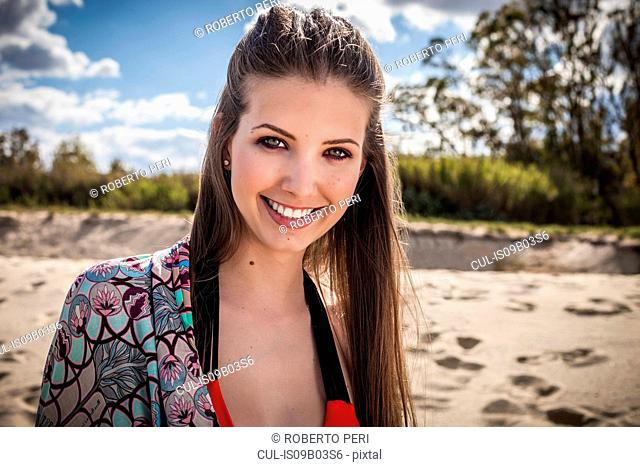 Portrait of beautiful young woman at beach, Costa Rei, Sardinia, Italy