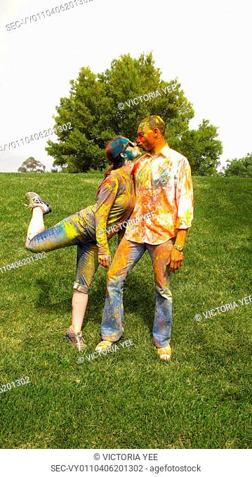 Couple covered in colorful paint kissing