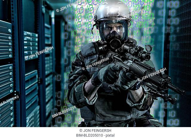 Soldier holding gun in server room