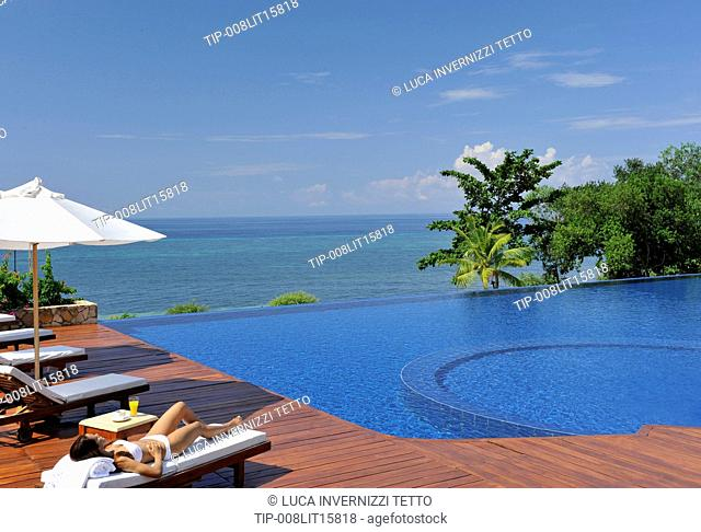 Philippines, Bohol, Eskaya Beach resort, woman by the poolside