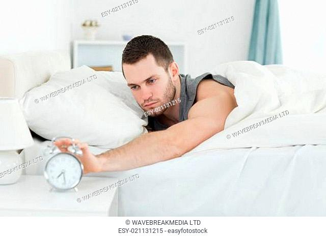 Tired man being awakened by an alarm clock