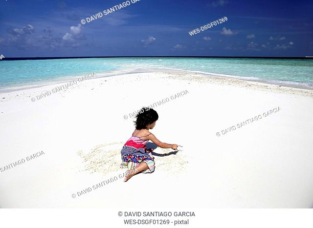 Maldives, girl on beach at shallow water