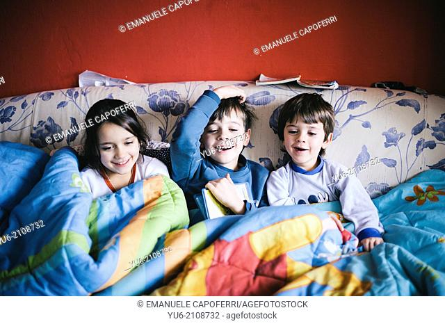 Three brothers children sitting on couch laughing