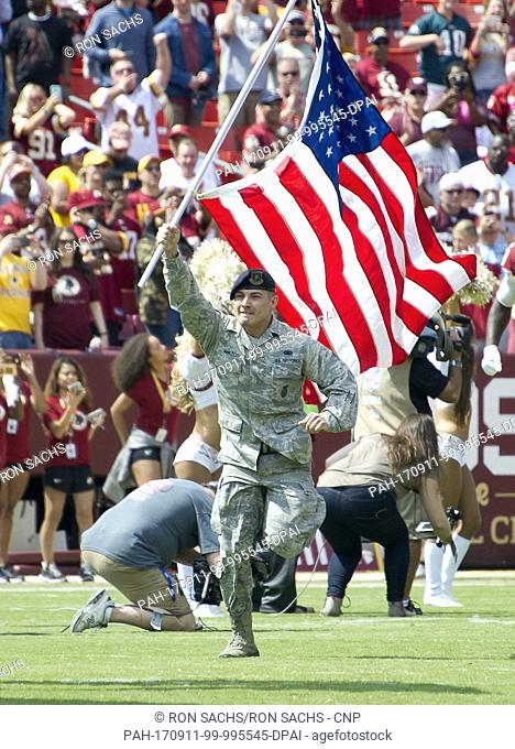A member of the United States Air Force runs onto the field carrying the American Flag prior to the Philadelphia Eagles against the Washington Redskins game at...