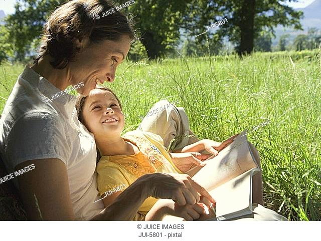 Mother reading storybook to daughter 8-10 in field, smiling, side view