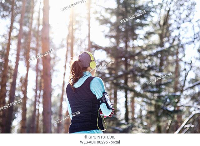 Back view of young jogger with headphones in forest having a break
