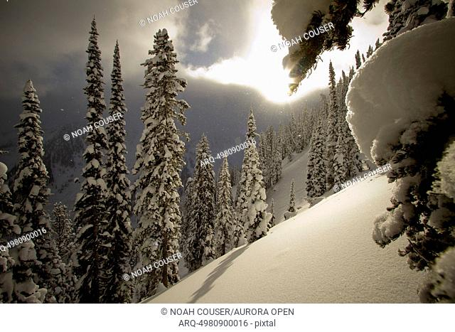 The sun peaks through the clouds illuminating a snowy slope in winter