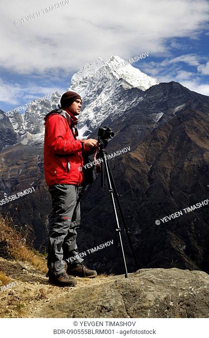 photographer on mountain top in Nepal Thamserku in background