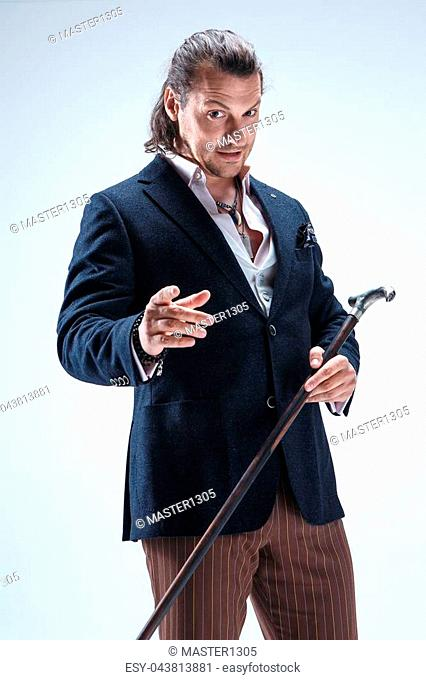 The mature bearded man in a suit holding cane. Isolated on a blue studio background