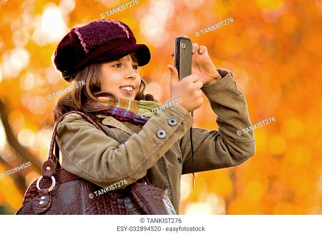 horizontal photo, happy beautiful little girl take a photograph on mobile phone, autumnal portrait