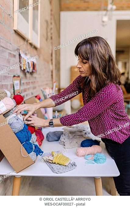 Woman at table choosing knitting wool from assortment