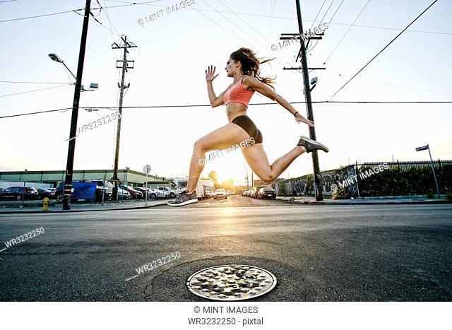 Female athlete running along street at dusk