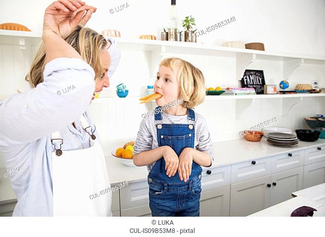 Mature woman and daughter mimicking rabbits with carrots in kitchen