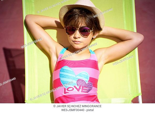 Young girl wearing swimwear, sunglasses and a sun hat, sitting in sun lounger