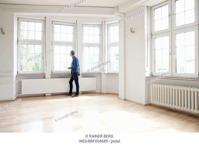 Man looking out of window in empty apartment