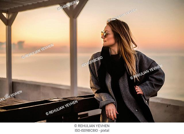 Portrait of woman wearing winter coat and sunglasses looking away, Odessa, Odeska Oblast, Ukraine