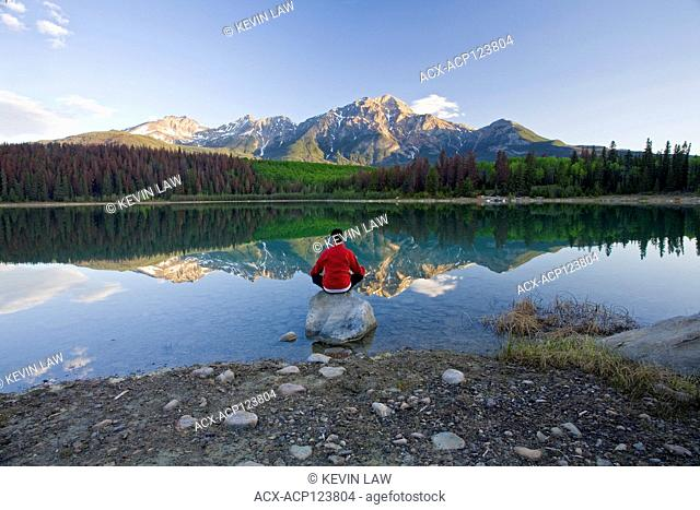 Middle age male meditating early morning at Pyramid Lake, Jasper National Park, Alberta, Canada