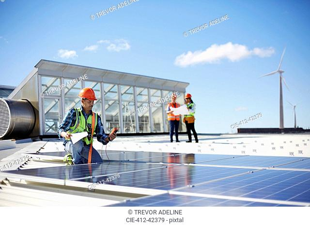 Engineer testing solar panels at sunny power plant
