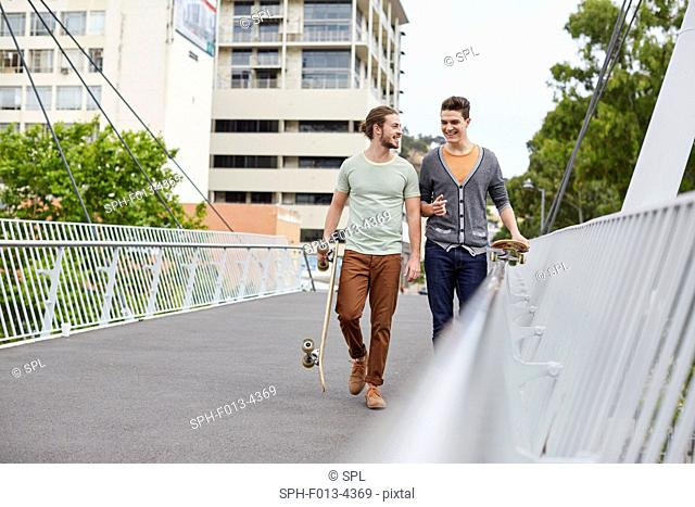 MODEL RELEASED. Two young men walking with skateboards