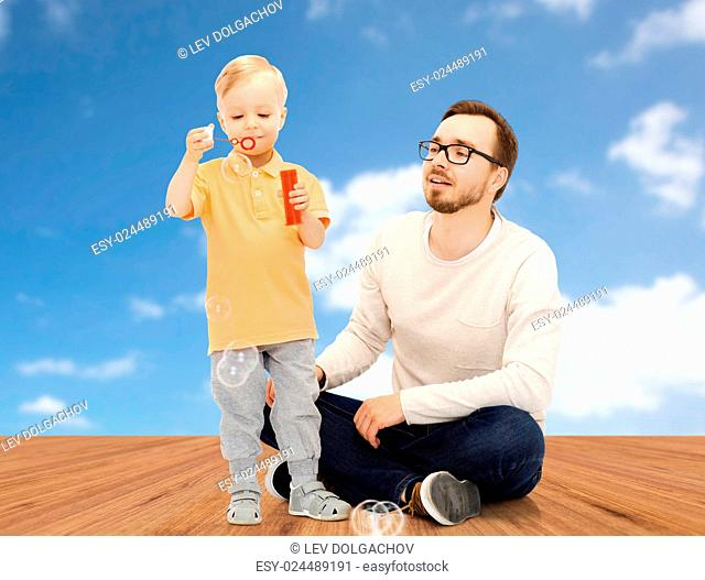 family, childhood, fatherhood, leisure and people concept - happy father and little son blowing bubbles and having fun over blue sky and wooden floor background