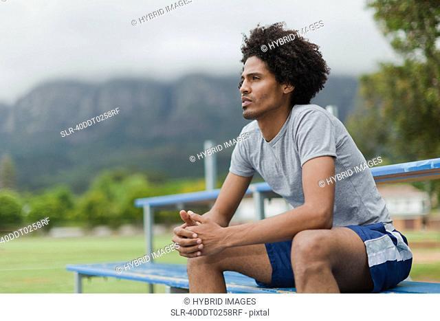Man sitting on bleachers in park