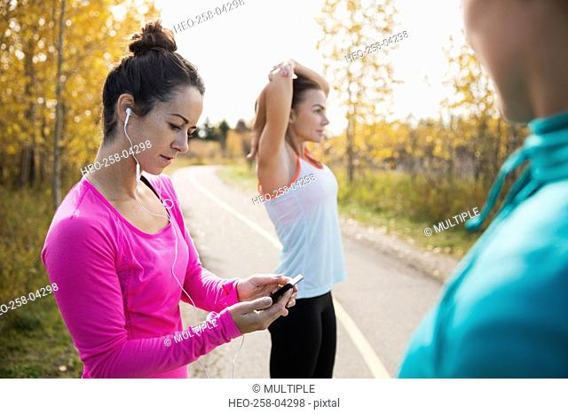 Jogger checking mp3 player on autumn path