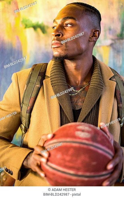 Black man wearing backpack holding basketball