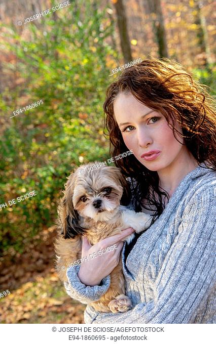 A 24 year old brunette woman holding and paling with Shih Tzu dog outdoors in the fall