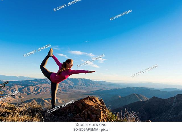 Young female trail runner in yoga pose on rock, Pacific Crest Trail, Pine Valley, California, USA