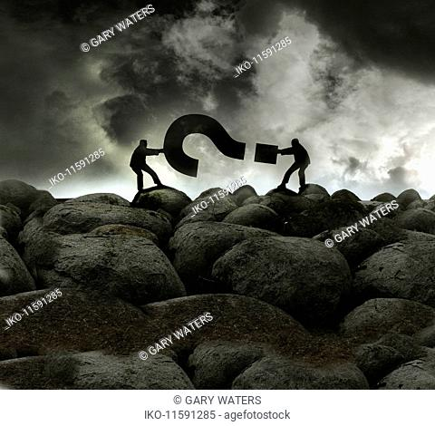 Two businessmen in tug of war with question mark