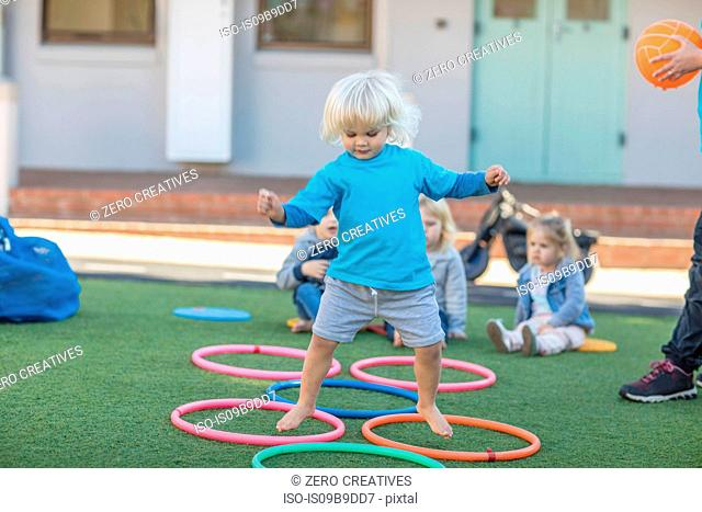 Girl at preschool, jumping above plastic hoops in garden