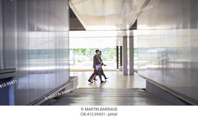 Business people walking in modern office corridor