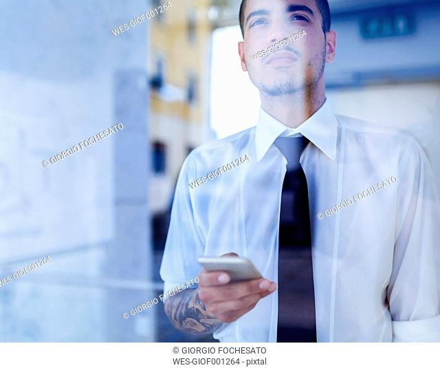 Young businessman behind glass pane