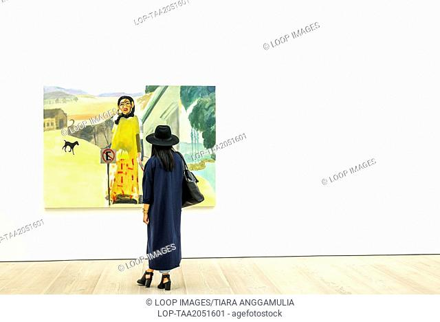 A woman admiring a painting inside the Saatchi Gallery