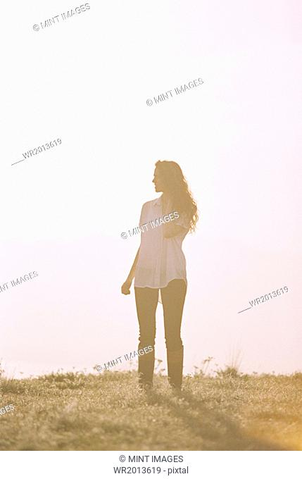 A woman alone standing on a hilltop