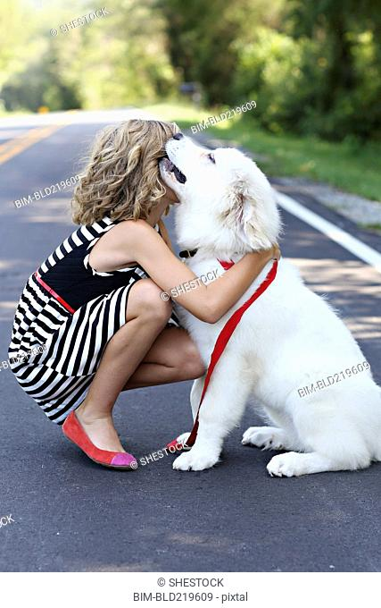 Close up of girl hugging dog on road