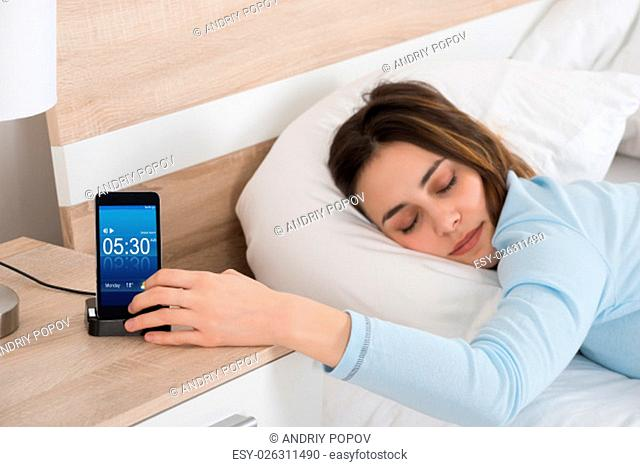 Woman Lying On Bed Snoozing Alarm On Mobile Phone