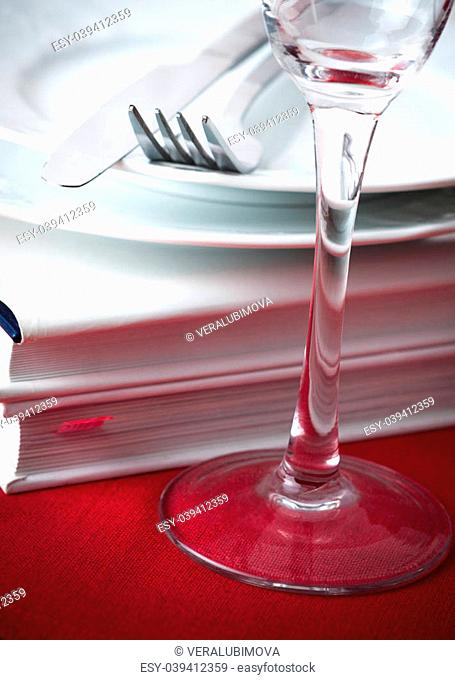 Two hardcover books with white covers underneath white china plates and silver cutlery with a wineglass to the fore
