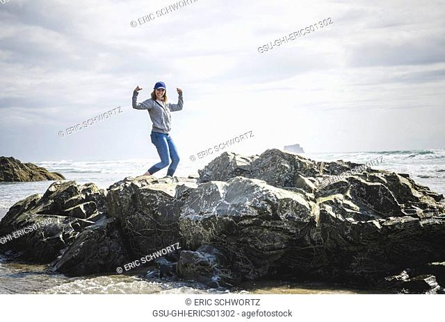 Young Woman Flexing on Rocky Formations, Hug Point State Park, Oregon, USA