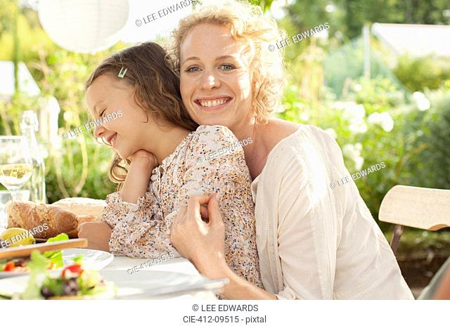 Mother and daughter smiling at table outdoors