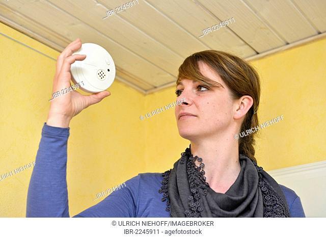 Woman holding a smoke detector