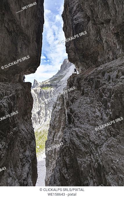 Italy, South Tyrol, Sexten, Hochpustertal, Bolzano. Hiker in silhouette on the Alpinisteig or Strada degli Alpini via ferrata, Sexten Dolomites