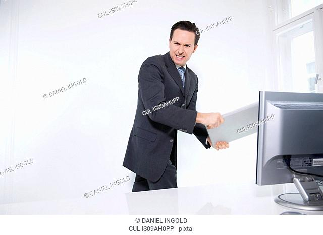 Businessman carrying off laptop from office
